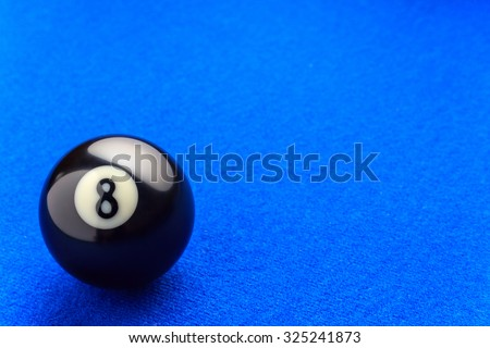 Eight billiard ball in a blue pool table.