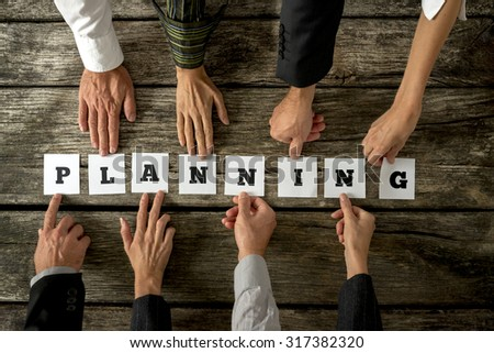 Eight business people assembling the word Planning with white cards with letters on them. Conceptual of teamwork and organization. - stock photo