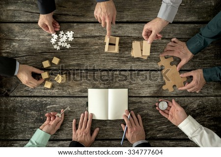 Eight businessmen planning a strategy in business advancement each holding  different but equally important metaphorical element - compass,  puzzle pieces, pegs, cubes, key and one making notes. - stock photo
