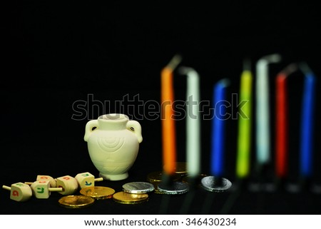 Eight candles are the symbol of the miracle happened on Hanukkah the Jewish holiday. In the background are oil pot, dreidel and golden coins, which are another symbol of the holiday. - stock photo
