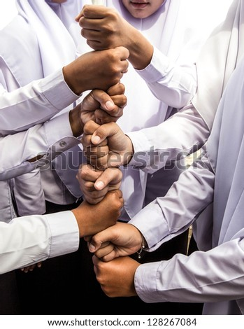 Eight clenched fists building a high tower - stock photo