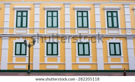 Eight close windows on yellow wall - stock photo