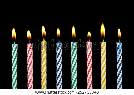 eight colorful birthday candles with flame on black