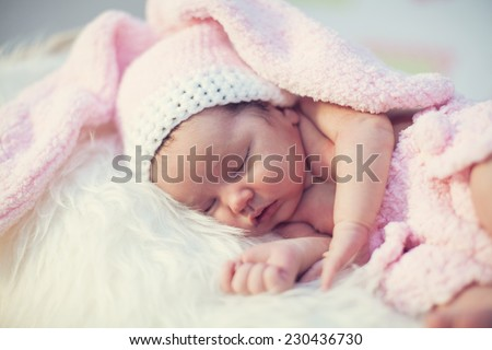 Eight day old newborn baby wearing bunny ears and a bunny tail diaper cover. she is sleeping on his stomach in a basket.  - stock photo