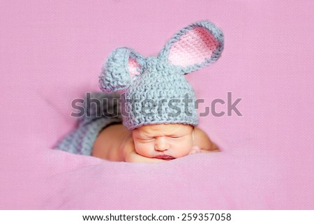Eight day old smiling newborn baby boy wearing bunny ears and a bunny tail diaper cover. He is sleeping on his stomach pink background - stock photo