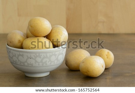 Eight fresh yellow potatoes in the small bowl and three on the table - stock photo