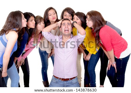 Eight Girls kissing a stressed man - stock photo