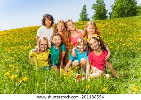 Eight kids sitting together on the green grass
