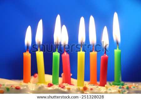 eight lit birthday candles close up, shallow dof