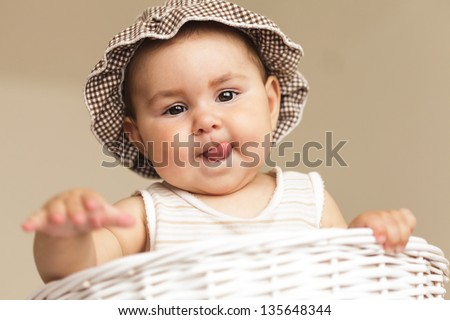 Eight month baby girl play with laundry basket - stock photo