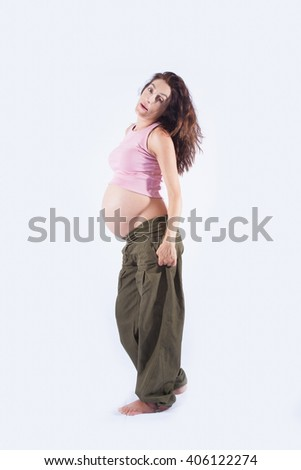 eight month pregnant brunette brown hair woman naked paunch pink shirt green trousers standing and looking isolated over white background - stock photo