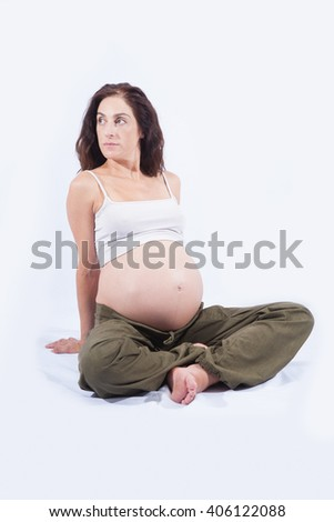 eight month pregnant brunette brown hair woman naked paunch white shirt green trousers sitting on floor resting and looking aside isolated over white background - stock photo