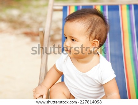 Eight months old baby boy sitting on a beach chair. - stock photo