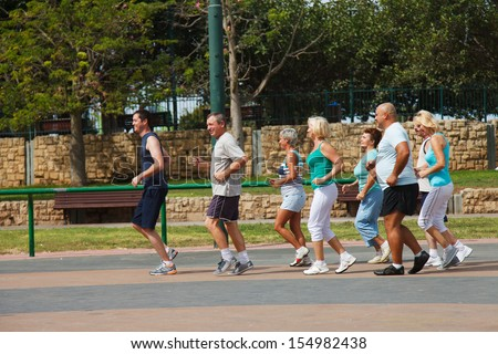 Eight people jogging in the park on a beautiful day