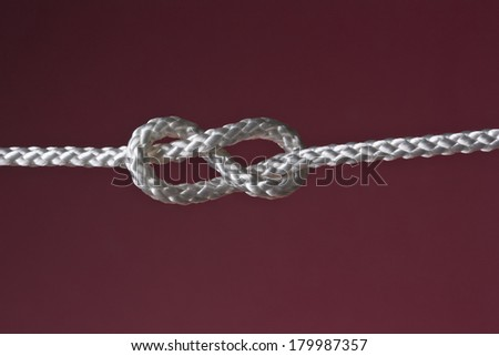 eight rope knot isolated on dark red background