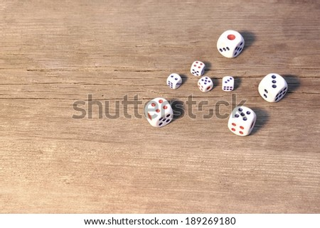Eight white dices on wooden floor or table, background with space for text or image - stock photo