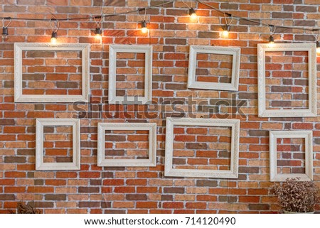 Eight White Empty Picture Frame Against Red Brick Wall Background With  Light Bulb Decorated In Wedding