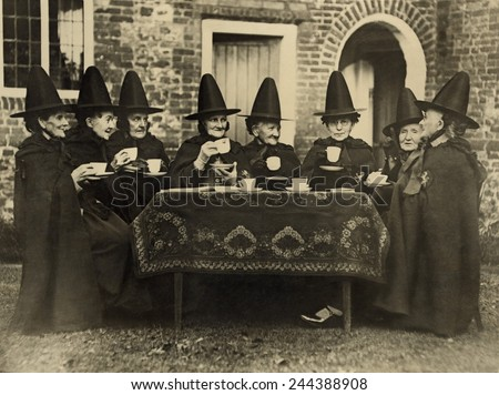 Eight women in high hats having tea. They are not a group of witches but the members of the Holy and Undivided Trinity of Castle Rising, Norfolk, England. Ca. 1920. - stock photo