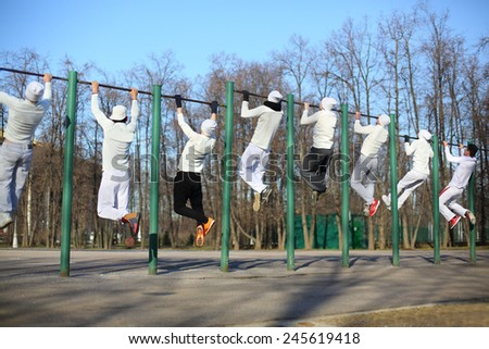 Eight young men coaching on the horizontal bar on the playground, view from the back - stock photo