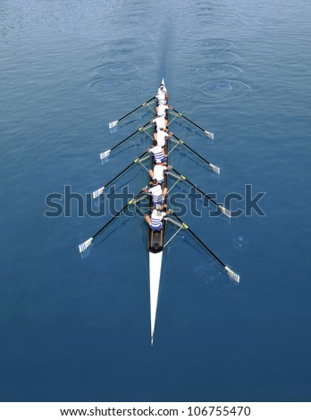 Eight young sportsmen rowing  on a sunny day