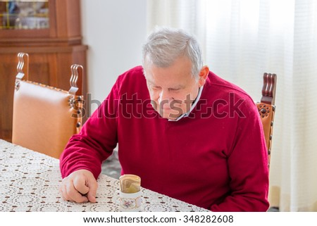 eighty-year-old man sitting at dining table holding euro banknotes in a coffee cup