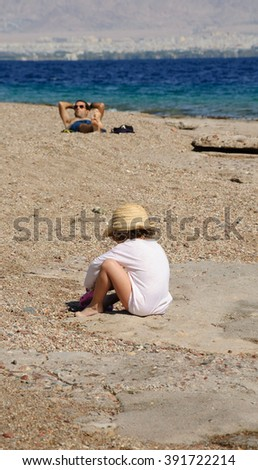 EILAT, ISRAEL - FEBRUARY 23, 2016: Girl and man relaxing at Coral Beach. Coral Beach Nature Reserve, one of the most beautiful coral reef in the world, is famous tourist and diver attraction. - stock photo