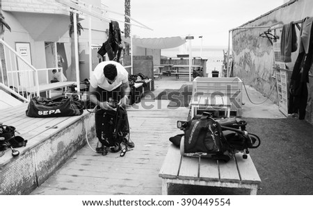 EILAT, ISRAEL - FEBRUARY 22, 2016: Man checks his equipment before a dive in Coral Beach Nature Reserve. This one of the most beautiful coral reef in the world is famous tourist and diver attraction. - stock photo