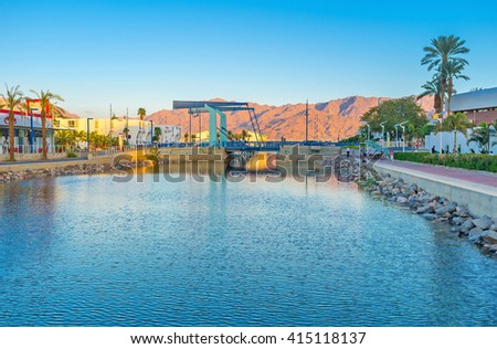 EILAT, ISRAEL - FEBRUARY 23, 2016: The drawbridge in New Lagoona of Eilat with the scenic mountains of Jordan in bright sunset lights, on February 23 in Eilat.