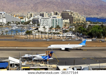 Eilat, Israel - MAY 17: plane of israeli airline Arkia, landed at the airport of Eilat on the background of luxurious hotels, Israel, on May 17, 2015 in  Eilat, Israel - stock photo