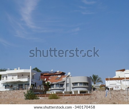 EILAT, ISRAEL - NOVEMBER 2 -  Small houses and clouds in the sky upon the Wadi Shahamon, copy space, on November 2, 2015 in Eilat, Israel