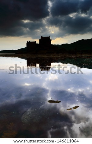 Eilean Donan Castle reflecting on Loch Duich just after Sunset as stormy dark clouds loom overhead. - stock photo