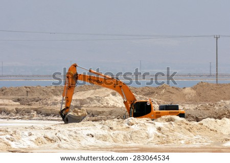 EIN BOKEK, ISR - APR 30 2015:Dead Sea Works bulldozer dig salt.It's the world's 4th largest potash products plant blamed by conservationists for polluting the Dead Sea environment and it's evaporation