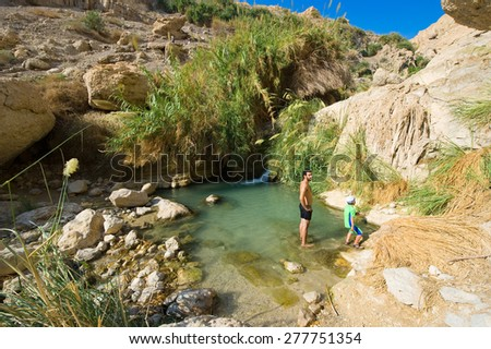 EIN GEDI, ISRAEL - OCT 15, 2014: A man and a child are relaxing in the water of the oasis Ein Gedi close to the dead sea in Israel - stock photo