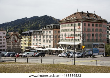 EINSIEDELN, SWITZERLAND - MAY 09, 2016: Colorful facades of buildings and cars on a street shows the town that is often visited by pilgrims and tourists because of the widely known Einsiedeln Abbey