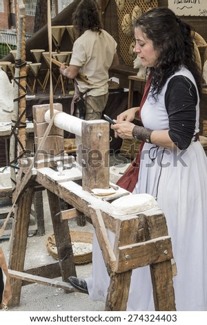 El Alamo, Madrid, Spain . May 1, 2015: A woman disguised as medieval personage works doing sculptures in stone on a medieval market in Spain