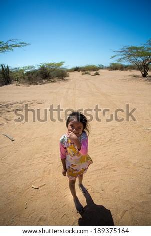 EL CABO DE LA VELA, COLOMBIA, JANUARY 15: Unidentified portrait of cute Wayuu Indian girl hiding her mouth in La Guajira, Colombia 2014. - stock photo