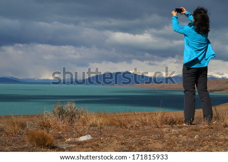 EL CALAFATE, ARGENTINA - DECEMBER 27, 2013 : Tourist woman pictures Lago Argentino. The lake lies within the Los Glaciares National Park and is the biggest freshwater lake in Argentina