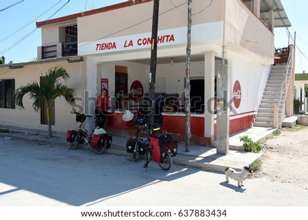 EL CUYO, MEXICO - JANUARY 22,2017: Cyclist taking a brake at a small shop in El Cuyo Mexico,January 22,2017.
