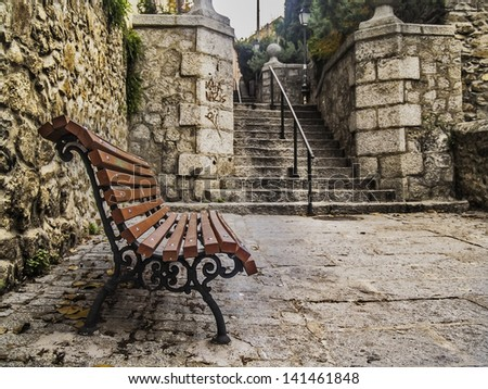 El Escorial, November 2012. Urban view, little square with a bench and stone stairs - stock photo