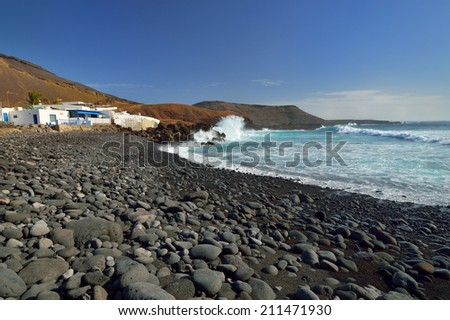 El Golfo village, white buildings and Atlantic Ocean shore with volcanic stones. Lanzarote Canary Islands. - stock photo