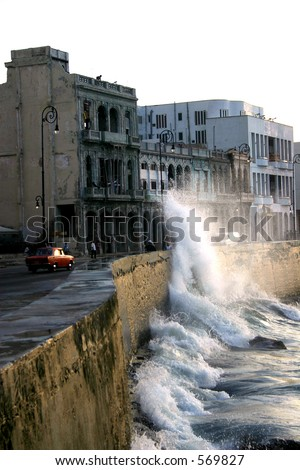 El Malecon de Havana; the famous Havana, Cuba seafront with waves crashing against the sea wall in front of the decaying buildings.