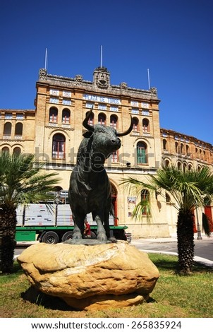 EL PUERTO DE SANTA MARIA, SPAIN - AUGUST 20, 2008 - Exterior view of the bullring (Plaza de Toros) with a bull statue in the foreground, El Puerto de Santa Maria, Andalusia, Spain, August 20, 2008. - stock photo