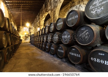 EL PUERTO DE SANTA MARIA, SPAIN - JULY 16: Wine Barrels in cellar of the famous Osborne Sherry Bodega. 16th July 2012 in El Puerto de Santa Maria, Andalusia Spain  - stock photo