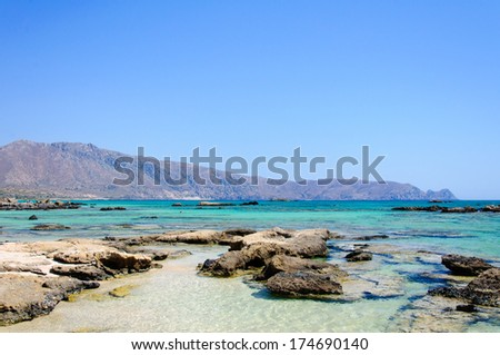 "Elafonisi or Elafonissi, ""deer island"" in Greek, is an island with turquoise water in the southwestern corner of the Mediterranean island of Crete, Greece. The island is a protected nature reserve. - stock photo"