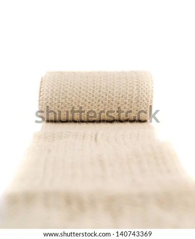 Elastic ACE compression bandage warp unwrapped over white background, shallow depth of field