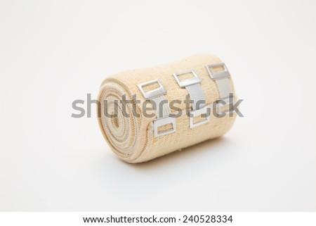 elastic bandage on a roll on white background - stock photo