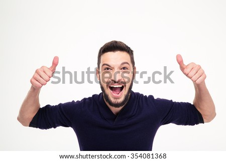 Elated excited young happy man with beard shouting and showing thumbs up with both hands over white background - stock photo