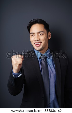 Elated young Asian businessman cheering his success punching the air with his fist with a beaming smile - stock photo