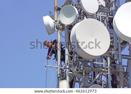 ELBA ISLAND , ITALY -20 JUNE 2016 : a worker installing telecommunications equipment on a trellis of antennas