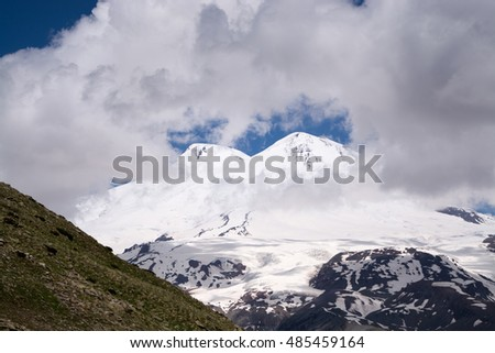 Elbrus - the highest mountain in Europe (5642 meters) and one of the 7 highest peaks in the World. Daytime. White clouds and blue sky. Sunny weather. A view of the whole mountain.